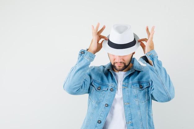 Mężczyzna w stylu retro trzyma palce na kapeluszu w kurtce, t-shirt i szuka ukryty. przedni widok.