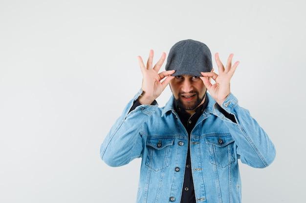 Mężczyzna w stylu retro, trzymając palce na czapce w kurtce, czapce, widok z przodu.