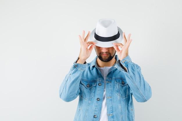 Mężczyzna w stylu retro, trzymając się za ręce na kapeluszu w kurtce, koszulce i mistyk.
