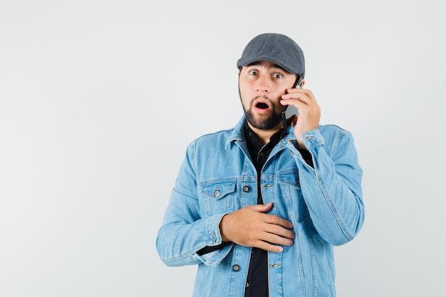 Mężczyzna w stylu retro w kurtce, czapce, koszuli rozmawia przez telefon komórkowy i wygląda przestraszony, widok z przodu. miejsce na tekst