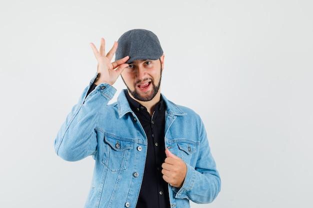 Mężczyzna w stylu retro w kurtce, czapce trzymającej palce na czapce, widok z przodu.