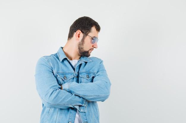 Mężczyzna w stylu retro w kurtce, okulary przeciwsłoneczne patrząc na bok stojąc ze skrzyżowanymi rękami, widok z przodu.