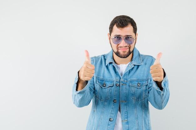 Mężczyzna w stylu retro w kurtce, okulary przeciwsłoneczne pokazujące kciuk i wyglądający imponująco, widok z przodu.