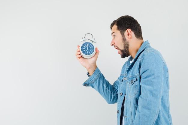 Mężczyzna w stylu retro w kurtce, t-shircie trzyma zegar i wygląda na zmartwionego.