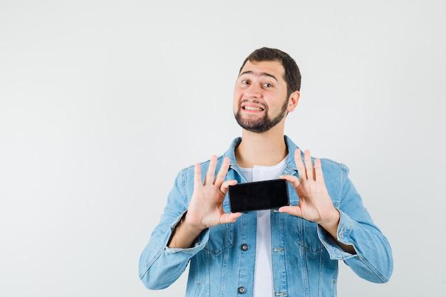 Mężczyzna w stylu retro w kurtce, t-shirt pokazujący telefon komórkowy i wyglądający na zadowolonego, widok z przodu.