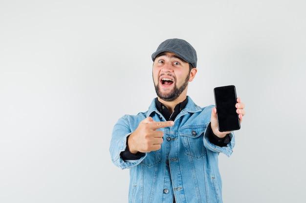 Mężczyzna w stylu retro w kurtkę, czapkę, koszulę, wskazując na telefon i patrząc wesoło, widok z przodu.