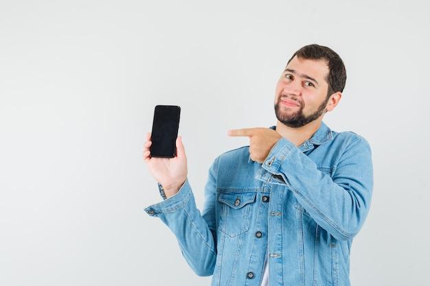 Mężczyzna w stylu retro, wskazując na telefon komórkowy w kurtce, t-shirt i wyglądający na zadowolonego. przedni widok.