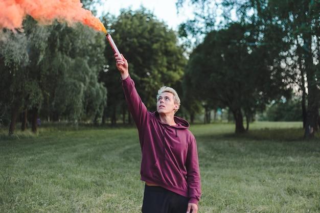 Mężczyzna w stylu ulicznym w bluzie z kapturem, trzymający flarę z czerwoną bombą z granatu dymnego.