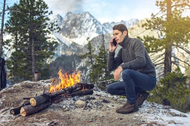 Mężczyzna w swetrze rozmawia przez telefon przy ognisku