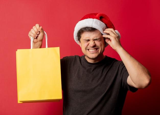 Mężczyzna w świątecznej czapce i czarnej koszulce z torby na zakupy na czerwonej przestrzeni