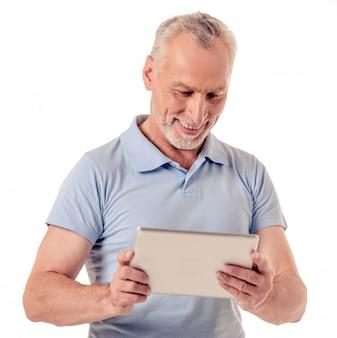 Mężczyzna w swobodnych ubraniach używa cyfrowego tabletu.