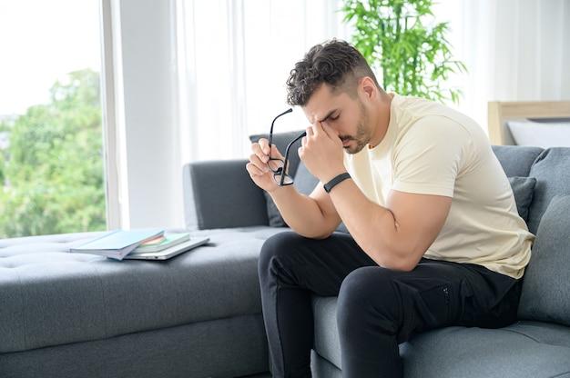 Mężczyzna w swobodnym ubraniu pracujący w domu, spotkanie online, rozmowa wideo, konferencja i nauka online ze stresem