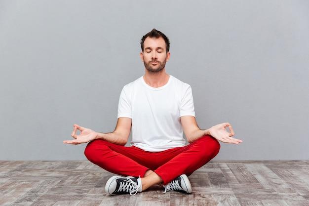 Mężczyzna w swobodnym ubraniu siedzący w pozycji lotosu na szarym tle