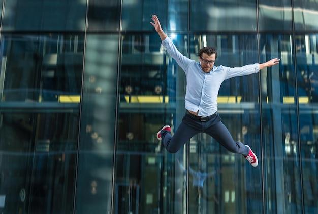 Mężczyzna w swobodnym ubraniu spada z nowoczesnego szklanego budynku