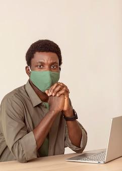 Mężczyzna w swoim miejscu pracy ma na sobie maskę medyczną