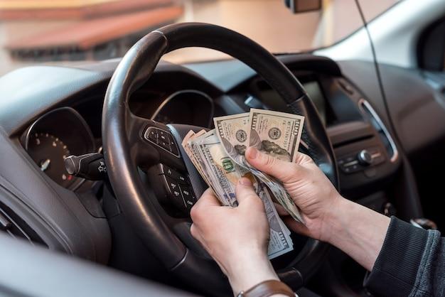 Mężczyzna w swoim samochodzie liczy nam rachunki do zapłaty. koncepcja finansów