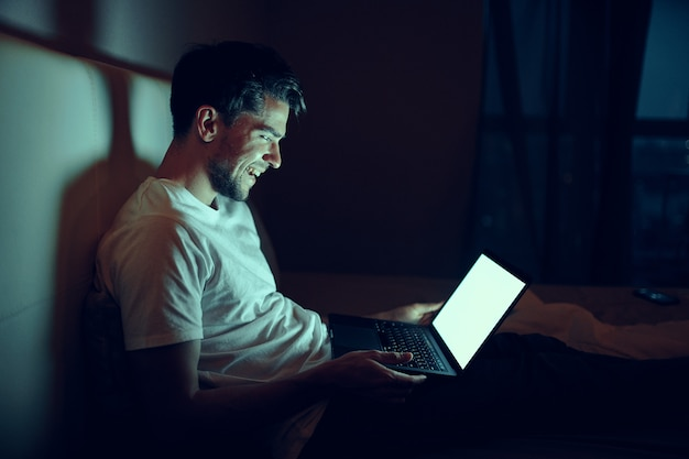Mężczyzna w sypialni w domu przed laptopem oglądając filmy w nocy