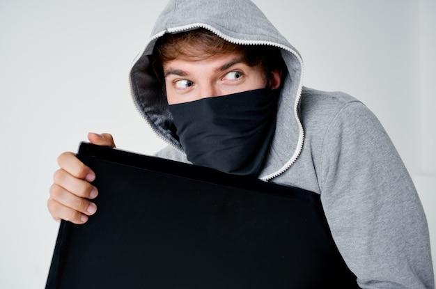 Mężczyzna w szarej bluzie z kapturem hakera w przebraniu kradzieży