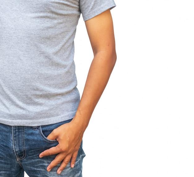 Mężczyzna w szarej koszulce i dżinsach trzyma ręce w kieszeniach