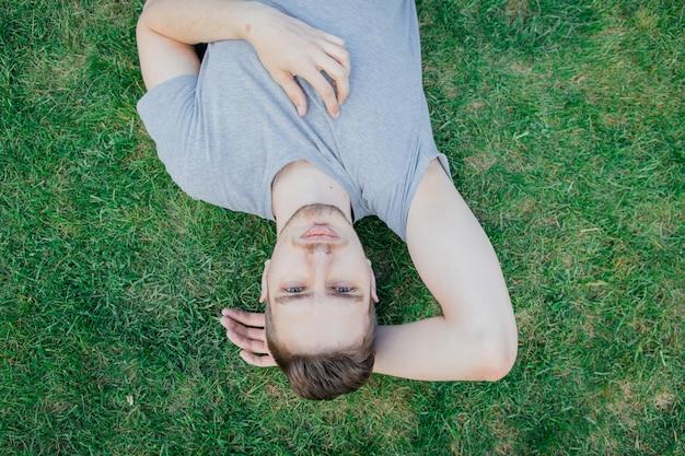 Mężczyzna w szarej koszulce leżący na zielonej trawie, lato. odpoczywający człowiek