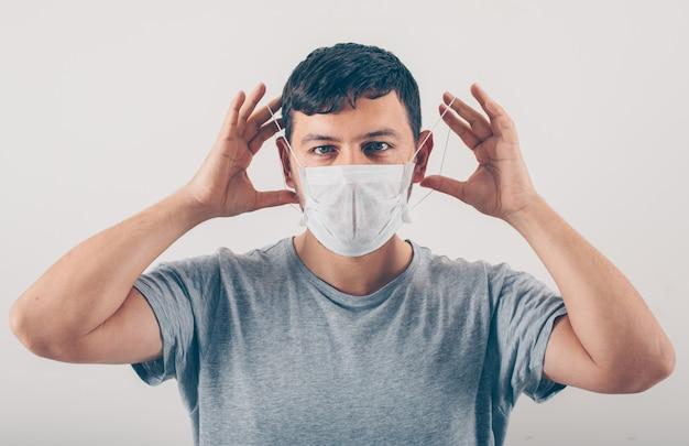 Mężczyzna w szarej koszulce noszący medyczną maskę w białym tle.