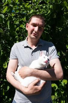 Mężczyzna w szarej koszulce trzyma w rękach białego kota na tle zielonych liści oświetlonych światłem słonecznym.