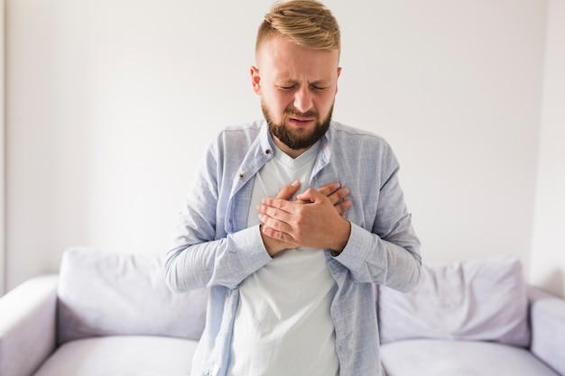 Mężczyzna w szarej koszuli cierpiących na ból serca