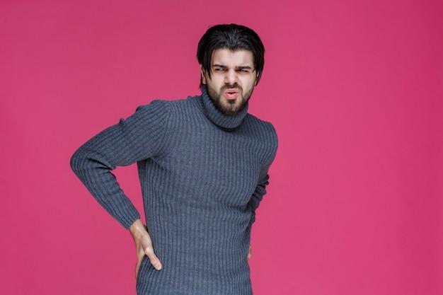 Mężczyzna w szarej koszuli trzyma się za ręce w talii, jakby miał ból pleców.