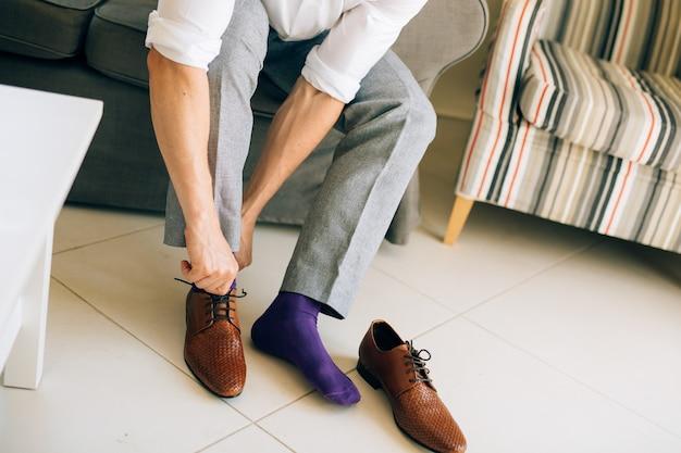 Mężczyzna w szarych spodniach i fioletowej sukience, skarpetkach, brązowych butach