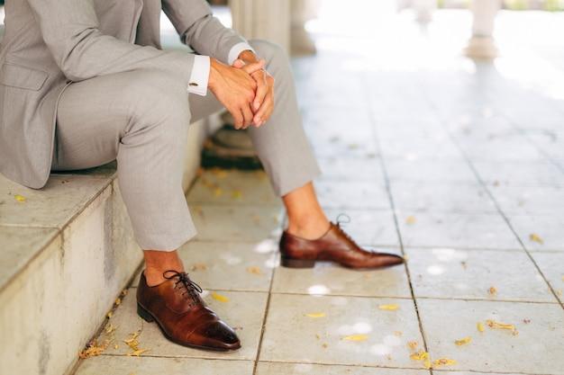 Mężczyzna W Szarym Garniturze I Brązowych Skórzanych Butach Siedzi Na Stopniu Ze Złożonymi Rękami Premium Zdjęcia
