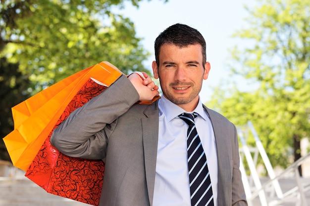 Mężczyzna w szarym garniturze z torby na zakupy