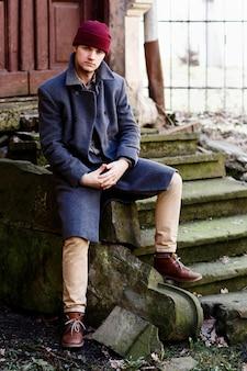 Mężczyzna w szarym płaszczu i beżowych spodniach siedzi na kamiennych śladach