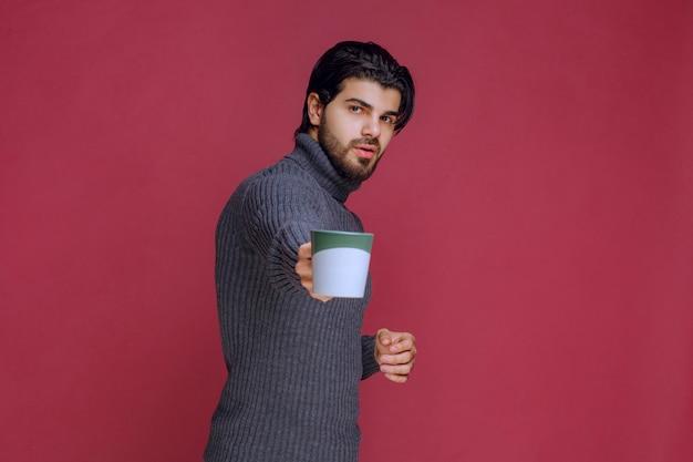 Mężczyzna w szarym swetrze oferujący kubek kawy.
