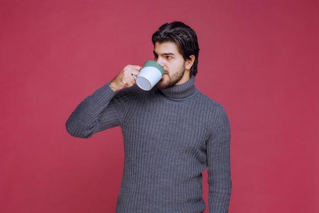 Mężczyzna w szarym swetrze pije kawę z kubka.