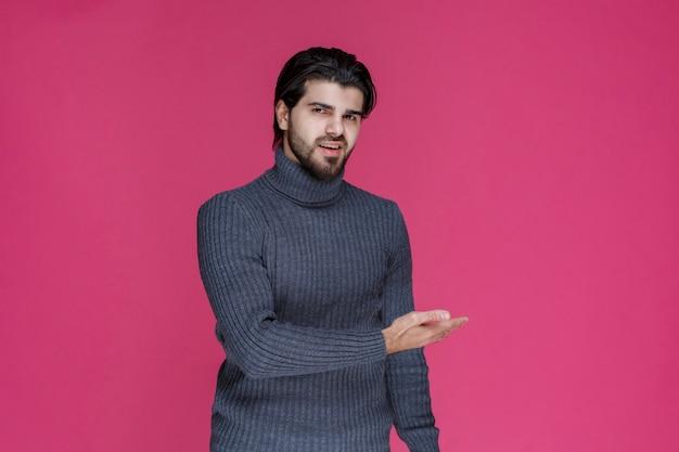 Mężczyzna w szarym swetrze przedstawiający lub witający kogoś z dużą energią i entuzjazmem.