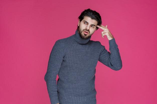 Mężczyzna w szarym swetrze przykłada palce do głowy, myśląc.