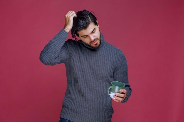 Mężczyzna w szarym swetrze trzyma kubek i myśli.