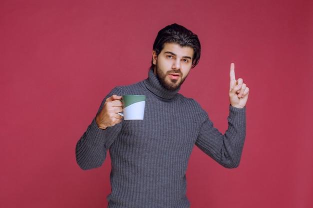 Mężczyzna w szarym swetrze trzyma kubek i prosi o uwagę.