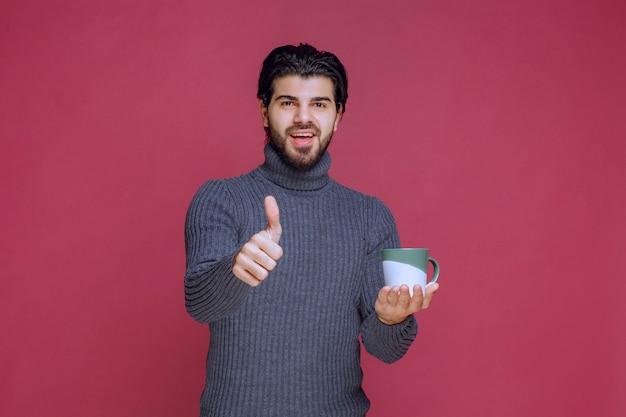 Mężczyzna w szarym swetrze trzyma kubek kawy i cieszy się smakiem.