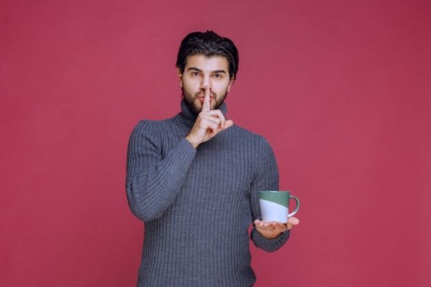 Mężczyzna w szarym swetrze trzyma kubek kawy i prosi o ciszę.