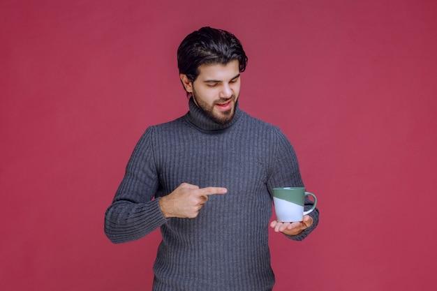 Mężczyzna w szarym swetrze trzyma kubek kawy i wskazuje go.