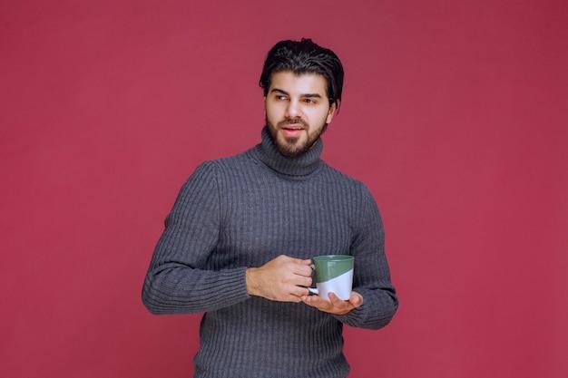 Mężczyzna w szarym swetrze, trzymając w ręku kubek kawy. wysokiej jakości zdjęcie