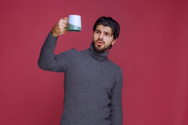 Mężczyzna W Szarym Swetrze, Trzymając W Ręku Kubek Kawy. Darmowe Zdjęcia
