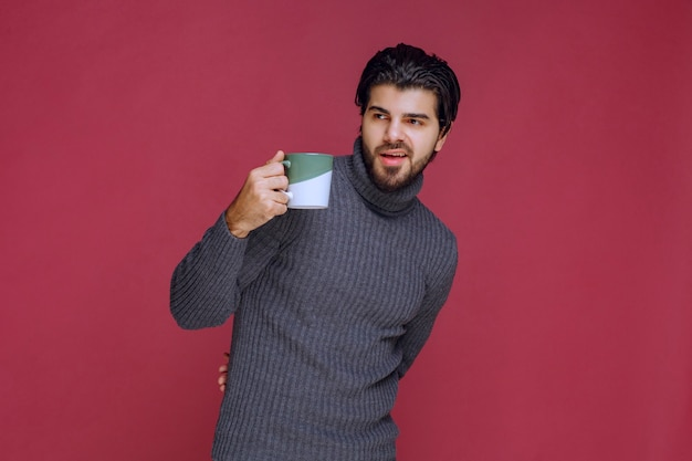 Mężczyzna w szarym swetrze, trzymając w ręku kubek kawy.
