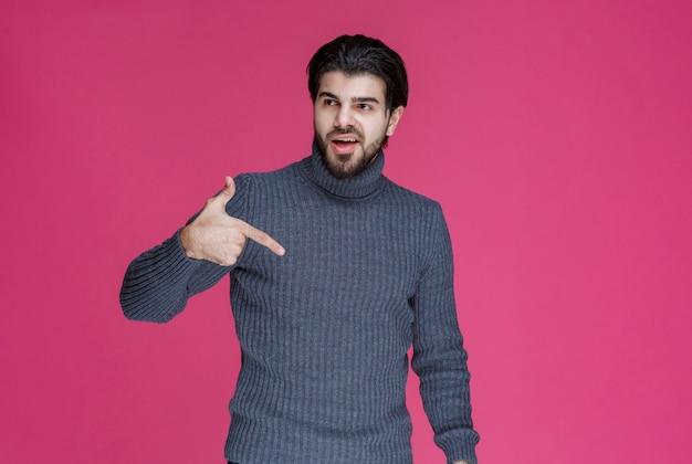 Mężczyzna w szarym swetrze wskazujący coś lub przedstawiający kogoś palcem wskazującym.