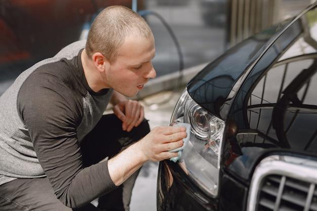 Mężczyzna w szarym swetrze wyciera samochód w myjni samochodowej