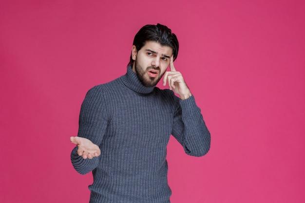 Mężczyzna w szarym swetrze z otwartymi rękami wygląda na niedoświadczonego.