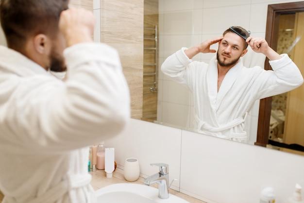 Mężczyzna w szlafroku czesze włosy w łazience