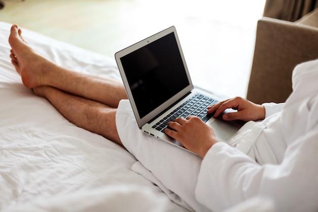 Mężczyzna w szlafroku leży na łóżku z komputerem na nogach praca na zlecenie z domu bez twarzy mężczyzna w ...