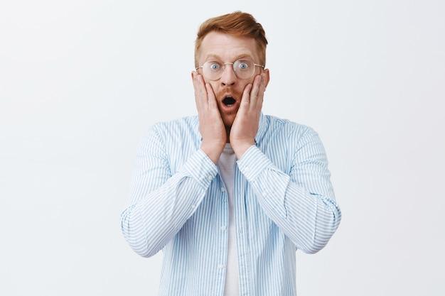 Mężczyzna w szoku jest świadkiem strasznej sceny. portret oszołomionego przerażonego rudowłosego mężczyzny w okularach i koszulach z opuszczoną szczęką, dyszącym ze zdumienia, wpatrującym się zmartwiony przez szarą ścianę
